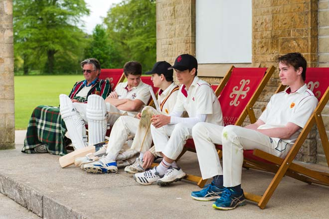 Cricketers on deck chairs outside