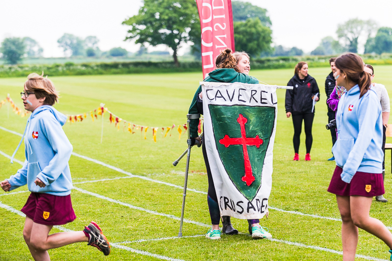 Girl on crutches with house flag as a cape at sports day 2018
