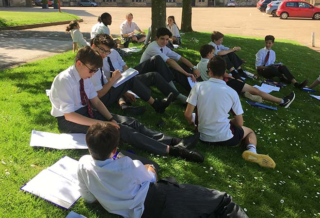 Students writing sonnets outside