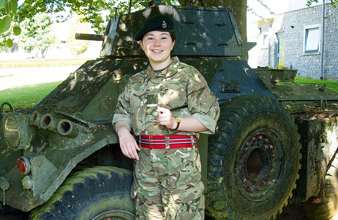Female CCF cadet next to tank